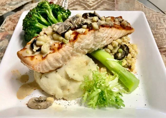 Grilled salmon Topped with a mushroom, Black olives, White corn cream sauce Garlic Mashed potatoes